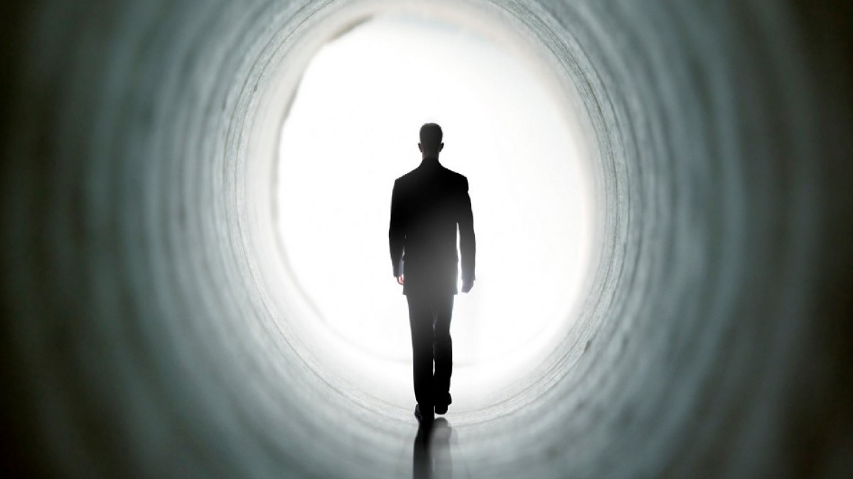 Hombre caminando hacia la luz.