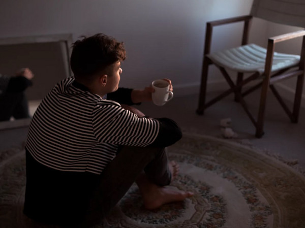 Adolescente sentado en el suelo de una habitación.