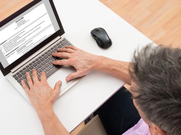 Hombre redactando un documento en un laptop.