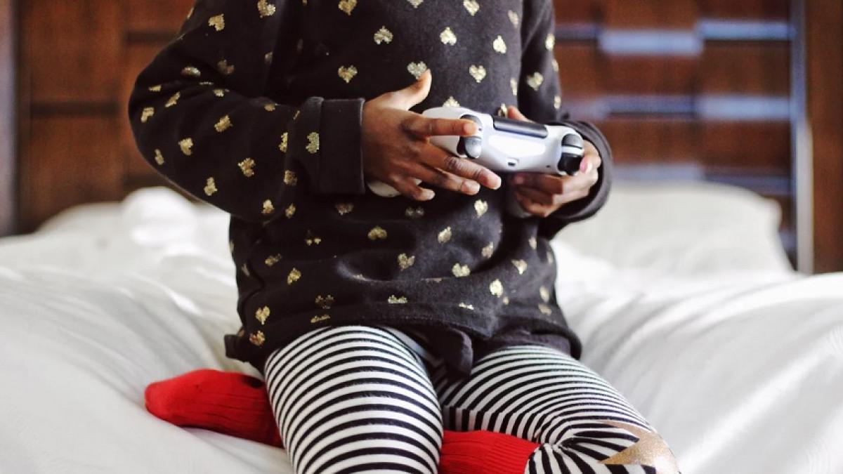 Niña pequeña jugando con una videoconsola.