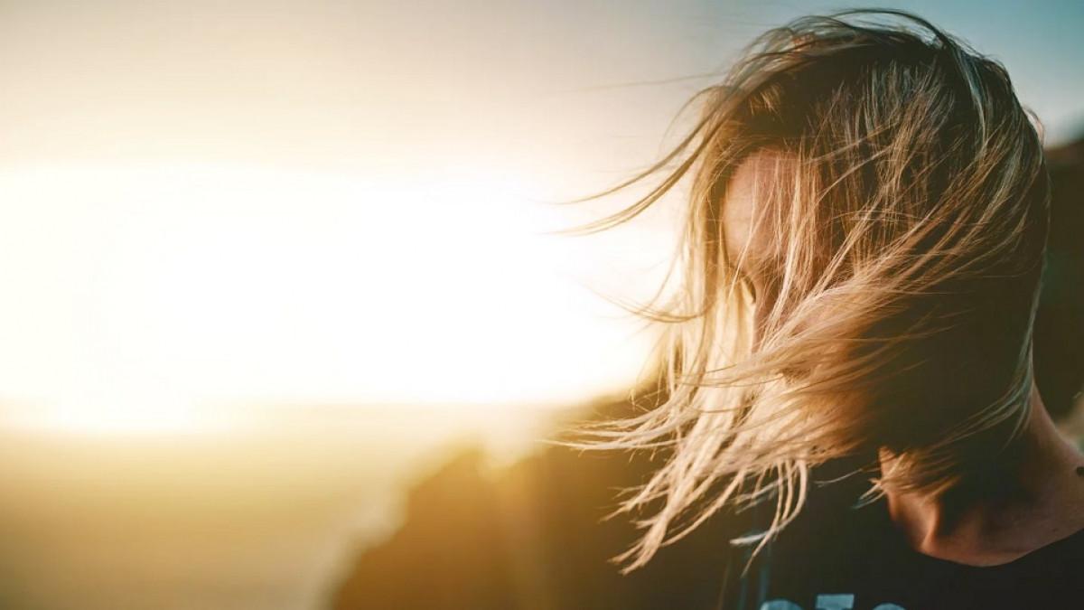 Mujer frente a una puesta de Sol.